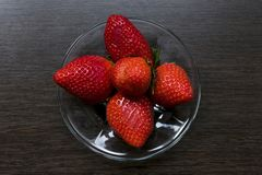 Strawberries on a saucer on the background of a wooden stand stock photo