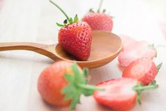 Strawberries. With selective focus on one berry placed on the bowl of a (wooden) spoon with others round about, some cut in half,  white background Stock Photo