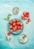 Strawberries  served in blue bowl with mint leaves and powdered sugar  on shabby chic wooden background. Top view Stock Images