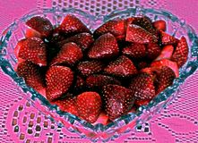 Strawberries in shape of heart. Closeup of ripe strawberries in heart shaped glass bowl on decorative pink background Royalty Free Stock Photography