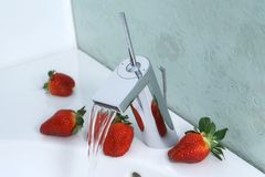 Strawberries and sink. Sink with running water lined with  strawberries Royalty Free Stock Images