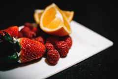 Strawberries and Sliced Wedge Oranges on White Dish Royalty Free Stock Images