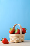 Strawberries in Small Basket against Blue Background Stock Photography