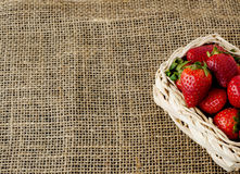 Strawberries in a small basket. On a jute table cloth, close up, text space stock photos