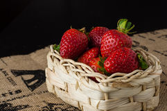 Strawberries in a small basket. On a jute table cloth with French motif print, close up stock image