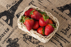 Strawberries in a small basket. On a jute table cloth with French motif print, close up stock photography