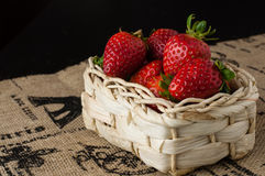 Strawberries in a small basket. On a jute table cloth with French motif print, close up, black background stock images
