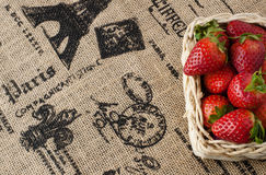 Strawberries in a small basket. On a jute table cloth with French motif print, close up, text space stock images