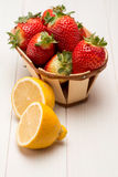 Strawberries in a small basket and lemon Royalty Free Stock Photography
