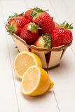 Strawberries in a small basket and lemon Royalty Free Stock Photos