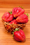 Strawberries in a small pottle on wooden table Royalty Free Stock Images