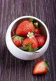 Strawberries in a small white bowl. Strawberries in a single small white bowl on dark stripe placemate Royalty Free Stock Image