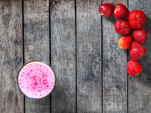 Strawberries and Smoothie. Strawberries and a glass of smoothie on a wooden background Royalty Free Stock Image