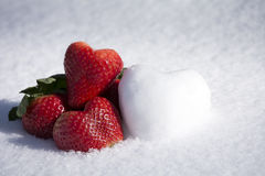 Strawberries and Snow Hearts Shape on White Snow Background Stock Photo