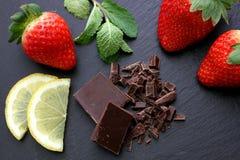 Strawberries, lemon slices, mint leaves and black chocolate on black slate background. Strawberries with some mint leaves, lemon slices and black chocolate on Stock Images