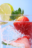 Strawberries in sparkly water with ice cubes Royalty Free Stock Photo