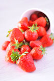 Strawberries spilling from a cup Stock Images