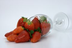 Strawberries spilling out of a glass Stock Image