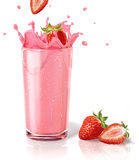 Strawberries splashing into a milkshake glass, with two others on the floor. Royalty Free Stock Image