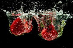 Strawberries splashing into water Stock Photography
