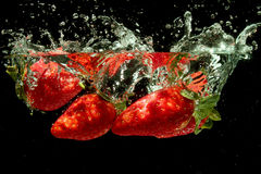 Strawberries splashing into water Royalty Free Stock Photos