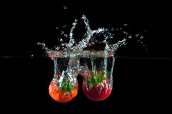 Strawberries splashing into water Royalty Free Stock Photography
