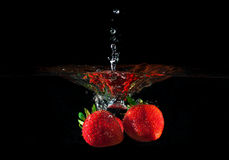 Strawberries splashing into water Stock Photo