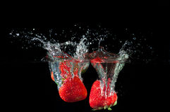 Strawberries splashing into water Royalty Free Stock Photo