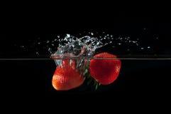 Strawberries splashing into water Stock Image