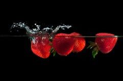 Strawberries splashing into water Royalty Free Stock Image