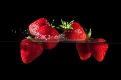 Strawberries splashing into water Royalty Free Stock Images