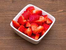 Strawberries on square bowl on wood Royalty Free Stock Images