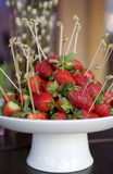 Strawberries with stick in vase on table Royalty Free Stock Images