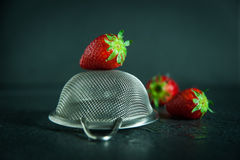Strawberries with strainer on dark background with water drops. Three strawberries with small stainless steel strainer on a dark background with water drops Royalty Free Stock Photo