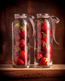 Strawberries in studio in glass jars. Strawberries in studio in two glass jars on wooden table and dark background Royalty Free Stock Photo