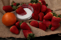 Strawberries, sugar and orange. Red whole strawberries, an orange fruit and a bowl with white sugar on raw jute Stock Image