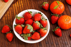 Strawberries and tangerines. Dish with fresh strawberries and some tangerines Stock Image