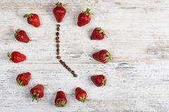 A strawberry clock with arrows from coffee beans showing a time of five or seventeen hours on a wooden vintage table in the kitche. Strawberries time - time for royalty free stock photo
