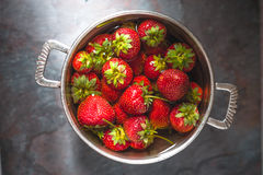 Strawberries in a tin bowl in the center of the table Royalty Free Stock Photos