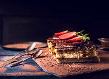 Strawberries tiramisu cake with three spoons on dark wooden Stock Photos