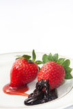 Strawberries topped with chocolate and strawberry syrup Royalty Free Stock Photos