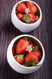 Strawberries in a two small white bowls. On dark stripe placemate Stock Photography