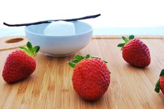Strawberries and vanilla bean whipped cream. On a wooden chopping board with real vanilla bean stock image
