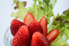 Strawberries and vegetable. Strawberries put in glass dish with vegetables and strawberries cut into pieces Stock Image
