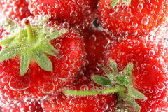 Strawberries in water with bubbles. Closeup stock photography