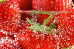 Strawberries in water close up. Strawberries in water with bubbles close up royalty free stock photos