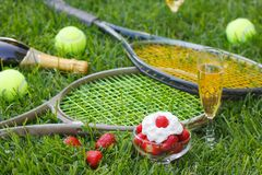 Strawberries with whipped cream, glass with champagne and tennis equipment on Wimbledon tournament grass. Wimbledon Grand slam celebration concept royalty free stock photos