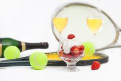 Strawberries with whipped cream, glasses with champagne and  tennis equipment on Wimbledon tournament. Wimbledon Grand slam celebration concept stock image