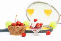 Strawberries with whipped cream, glasses with champagne and  tennis equipment on Wimbledon tournament. Wimbledon Grand slam celebration concept stock photo