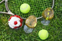 Strawberries with whipped cream, glasses with champagne and tennis equipment on Wimbledon tournament grass. Wimbledon Grand slam celebration concept. Top view stock photos